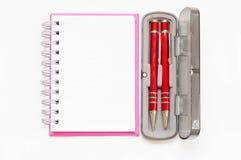 Caderno cor-de-rosa com a pena de dois vermelhos na caixa no fundo branco Imagem de Stock