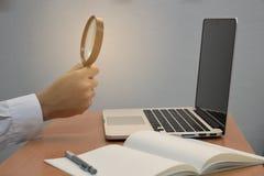 Caderno da busca da lupa da terra arrendada da mão do negócio e portátil ou computador masculino para o conceito criativo da idei imagem de stock