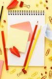 Caderno da escola e vários artigos de papelaria vermelhos e amarelos fotos de stock royalty free