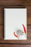 Caderno da receita, alho, pimentão vermelho no fundo de madeira fotografia de stock