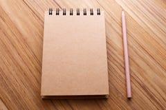 Caderno da tampa de Kraft na tabela de madeira imagens de stock royalty free