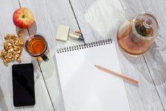 Caderno de papel, lápis, copo do chá, maçã, telefone celular e nozes na tabela de madeira Imagens de Stock