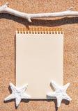Caderno de papel, ramo seco e conchas do mar na areia Imagens de Stock Royalty Free