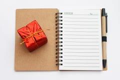 Caderno do ano novo e do Natal com uma caixa atual vermelha Fotografia de Stock