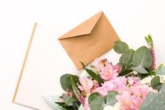 Caderno do ofício do vintage ou diário aberto com a decoração macia das flores e envelope fechado do ofício na tabela branca fotos de stock royalty free