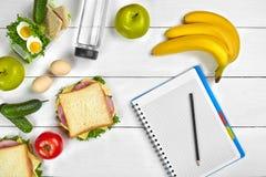 Caderno do planeamento da vista superior com espaço da cópia e sanduíche saudável do café da manhã com presunto e queijo, ovos, p Fotografia de Stock Royalty Free