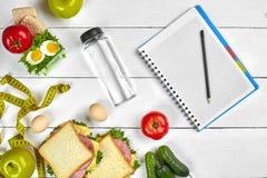 Caderno do planeamento da vista superior com espaço da cópia e sanduíche saudável do café da manhã com presunto e queijo, ovos, p Imagem de Stock