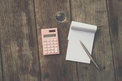 Caderno e calculadora brancos pequenos na textura velha da madeira do grunge foto de stock