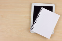 Caderno e dispositivo eletrónico de papel na tabela de madeira Imagem de Stock