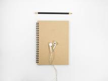 Caderno e fone de ouvido do marrom da vista superior Fotografia de Stock Royalty Free