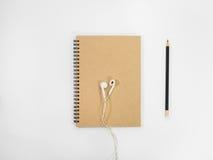 Caderno e fone de ouvido do marrom da vista superior Foto de Stock