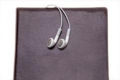 Caderno e fones de ouvido brancos isolados no fundo branco foto de stock royalty free