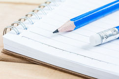 Caderno e lápis do close-up na tabela de madeira Imagem de Stock