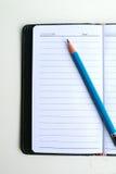 Caderno e lápis portáteis Imagem de Stock