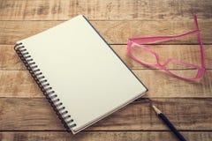 Caderno e lápis vazios com vidros em uma tabela de madeira Fotografia de Stock