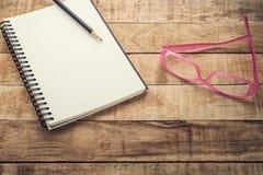 Caderno e lápis vazios com vidros em uma tabela de madeira Imagens de Stock Royalty Free