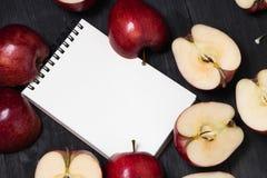 Caderno e maçã em uma opinião superior do fundo de madeira preto Imagem de Stock Royalty Free