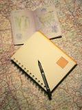 Caderno e passaporte em um mapa Imagem de Stock