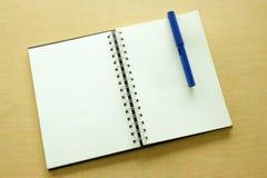 Caderno e pena azul Imagens de Stock