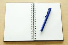 Caderno e pena azul Fotografia de Stock Royalty Free