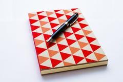 Caderno e pena coloridos no branco fotografia de stock royalty free