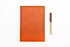 Caderno e pena de Brown isolados no branco Fotos de Stock Royalty Free