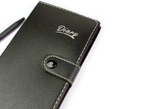 Caderno e pena de couro pretos no fundo branco Fotografia de Stock