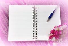 Caderno e pena em um fundo cor-de-rosa Fotos de Stock