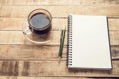 Caderno e pena vazios com café em uma tabela de madeira Fotos de Stock Royalty Free