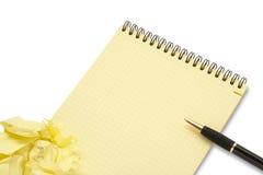 Caderno e wad de papel amarrotado com pena imagem de stock