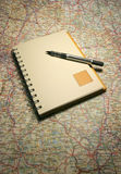 Caderno em um mapa Imagem de Stock Royalty Free