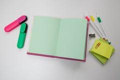 Caderno entre as penas e os marcadores Imagens de Stock Royalty Free