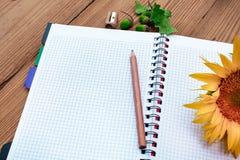 Caderno espiral aberto com lápis e girassol Imagens de Stock