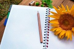 Caderno espiral aberto com lápis e girassol Fotografia de Stock Royalty Free