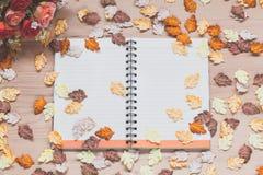 Caderno espiral com as folhas de bordo no fundo de madeira Fotos de Stock Royalty Free