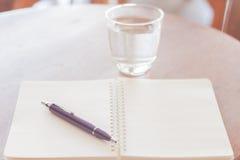 Caderno espiral da pena e da placa na tabela de madeira Fotografia de Stock