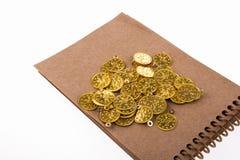 Caderno espiral e as moedas de ouro Fotografia de Stock