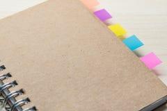 Caderno fechado com nota colorida da etiqueta Foto de Stock