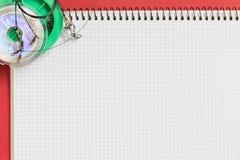 Caderno grande com os equipamentos de pesca no fundo do papel da cor Fotografia de Stock Royalty Free