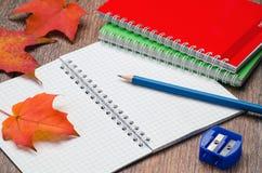 Caderno, lápis, apontador e folhas de outono na tabela Imagens de Stock Royalty Free