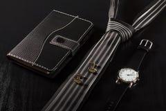 Caderno, laço, botão de punho, relógio em um fundo preto Imagens de Stock