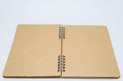 Caderno liso marrom aberto com fundo branco e foco seletivo Imagens de Stock Royalty Free
