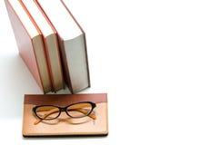 Caderno, livros e vidros no fundo branco Fotografia de Stock