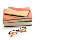 Caderno, livros e vidros no fundo branco Foto de Stock