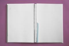 Caderno no fundo violeta Fotografia de Stock Royalty Free