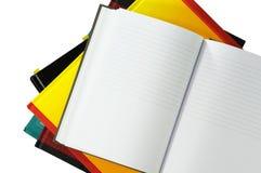 Caderno nos livros isolados no branco Fotografia de Stock Royalty Free