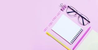 Caderno ou bloco de notas com vidros e fones de ouvido do olho no backgriund cor-de-rosa Conceito criativo da chancery do minimal imagens de stock