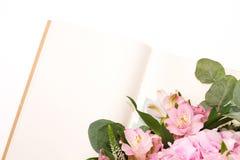 Caderno ou diário aberto do ofício do vintage com a decoração macia das flores na tabela branca imagem de stock
