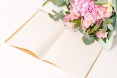 Caderno ou diário aberto do ofício do vintage com a decoração macia das flores na tabela branca imagens de stock royalty free