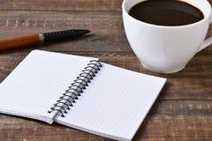 Caderno, pena e chávena de café vazios imagem de stock royalty free